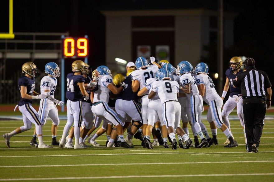 Players from both Spain Park and Briarwood swarm the ball carrier during a play late in the first half. Social distancing on the sidelines is emphasized but impossible on the field.