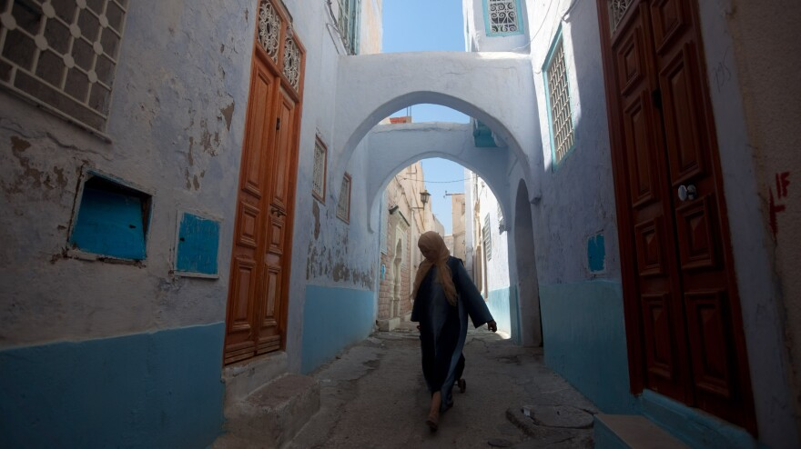 A woman walks the narrow streets of the old city in Kairouan, Tunisia.