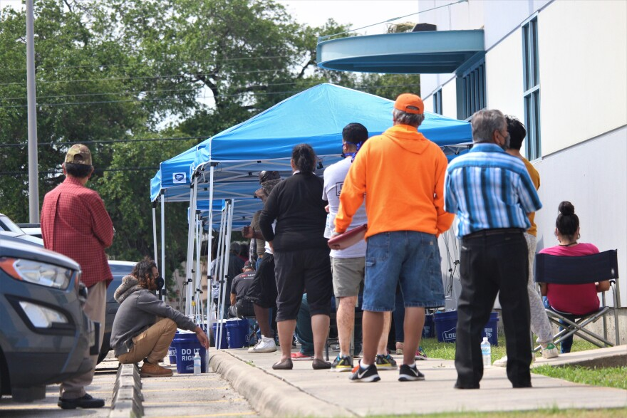 People wait in line to be tested for COVID-19 at a pop-up site outside of Las Palmas Library in San Antonio.