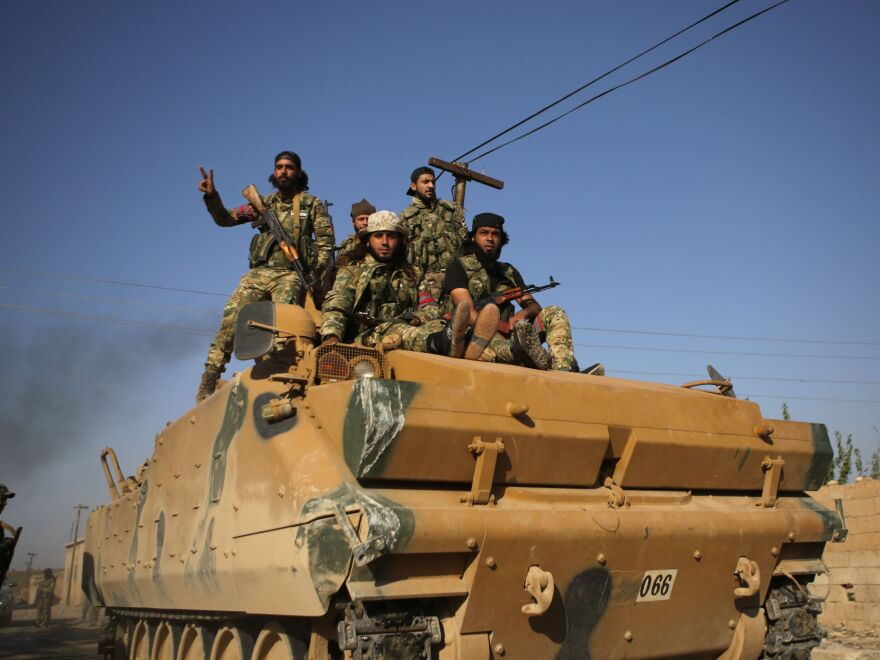 Turkey-backed Syrian fighters sit atop an armored personnel carrier in the southwestern neighborhoods of the border Syrian town of Tal Abyad on Sunday. The U.S. plans to evacuate its troops from northern Syria amid the Turkish offensive.