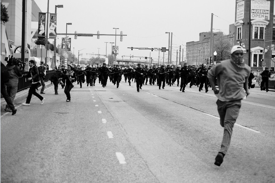 "A man runs from a line of charging police in riot gear in Baltimore. The photo, taken by Devin Allen, is featured in the National Museum of African American History and Culture's newest exhibit, ""More Than A Picture."""