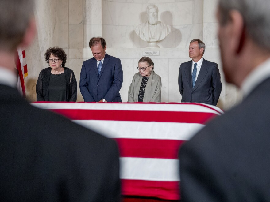 Supreme Court Justices Sonia Sotomayor (from left), Samuel Alito, Ruth Bader Ginsburg and John Roberts participate in a moment of silence during a private ceremony in the Great Hall of the Supreme Court, where the body of the late Supreme Court Justice John Paul Stevens lies in repose.