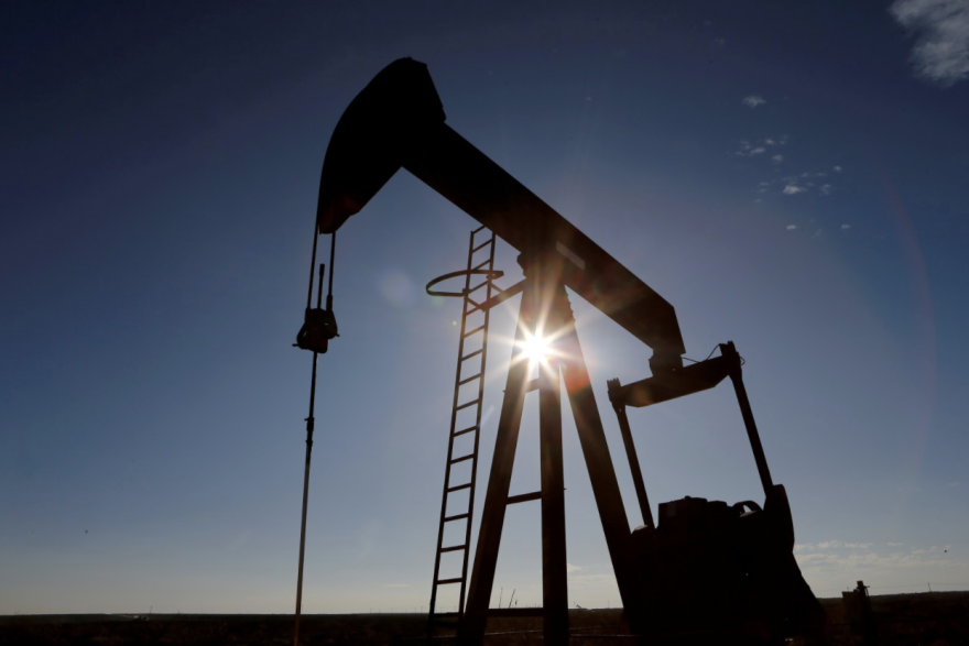 The sun is seen behind a crude oil pump jack in the Permian Basin in Loving County, Texas.