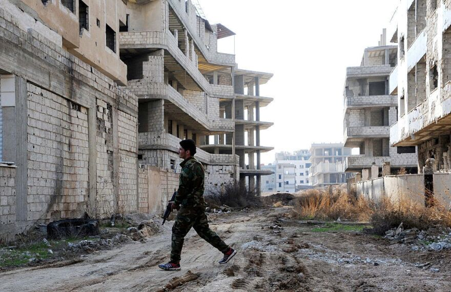 A Syrian soldier walks on a ravaged street in Daraya, a besieged suburb of Syria's capital, in February.