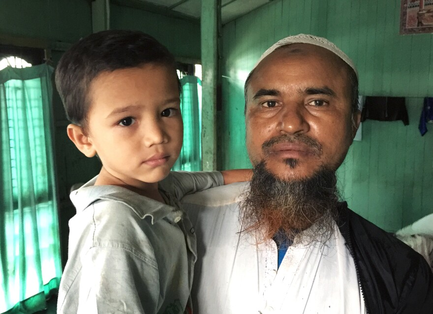 Habibullah, a longtime Aung Mingalar resident who goes by one name, holds his 4-year-old son Mohammed Harris at his home. He says his son, lacking adequate nutrition and running a fever for four weeks, has become too weak to walk.