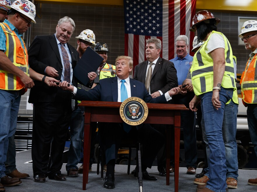 President Trump hands out pens after signing an executive order aimed at making it easier for companies to pursue oil and gas pipeline projects. The president addressed an audience at the International Union of Operating Engineers International Training and Education Center in Texas.