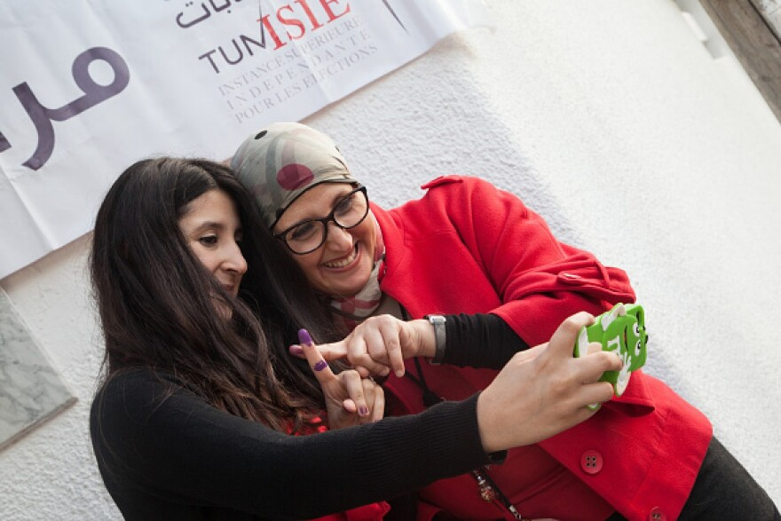 Tunisian citizens take a selfie with their inked fingers after casting their votes at a polling station during the Tunisian Presidential Election on Sunday.