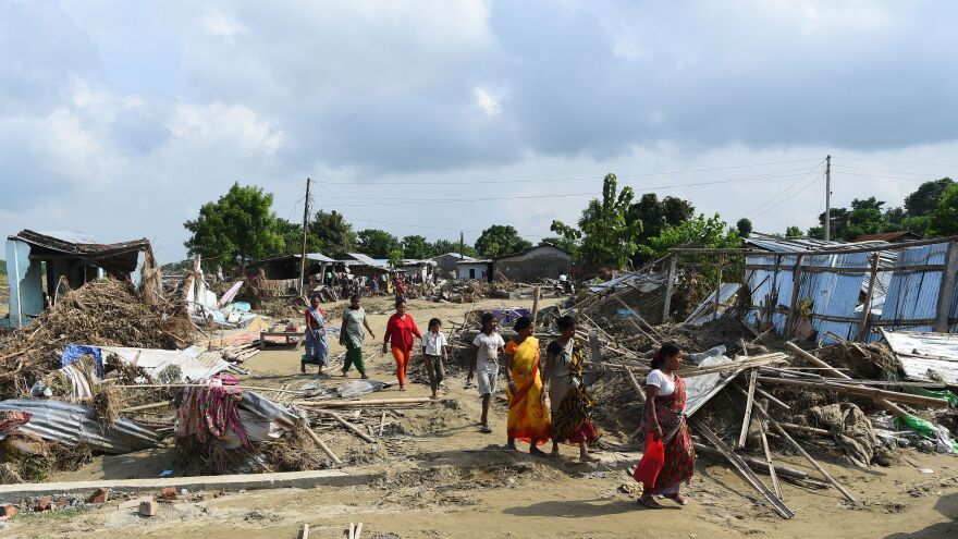 Flood victims walk past damaged houses in Itahari, Sunsari district, Nepal, earlier this month. Severe flooding has left tens of thousands of homes totally underwater in the populous southern lowlands of Nepal.
