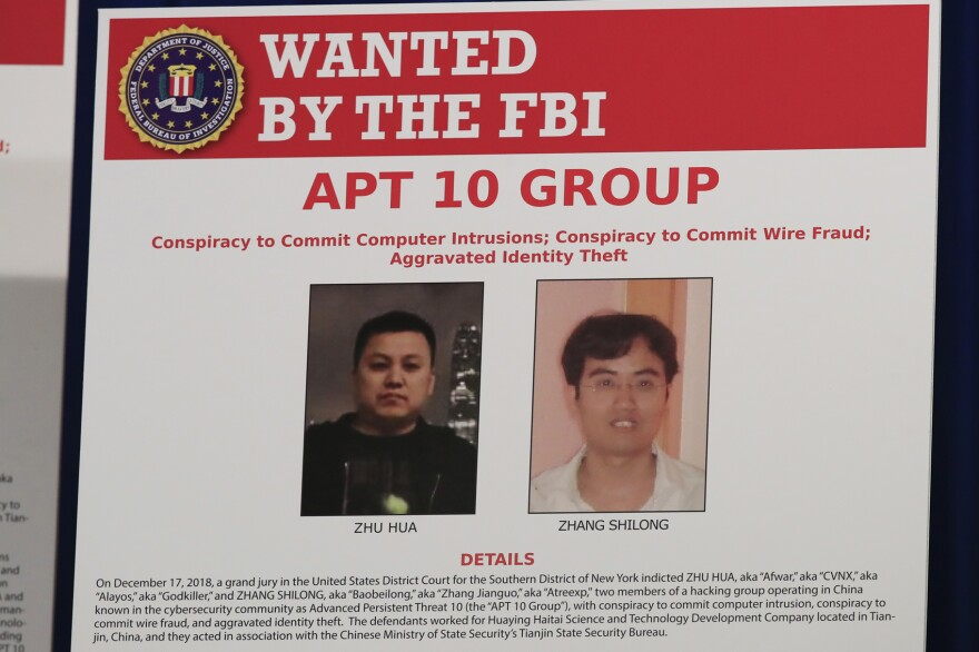 A poster displayed during a news conference at the Department of Justice in Washington, Thursday, Dec. 20, 2018, shows two Chinese citizens suspected to be with the group APT 10 carrying out an extensive hacking campaign to steal data from U.S. companies. (Manuel Balce Ceneta/AP)