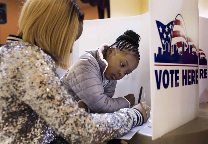 Jumira Moore, 8, watches as her mother, Timira Saunders, fills out a ballot at Central Baptist Church in St. Louis on Tuesday, Nov. 8, 2016.