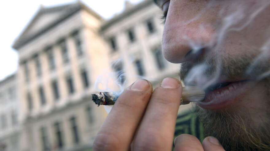 A man smokes marijuana outside Uruguay's parliament in Montevideo on Wednesday, where lawmakers in the lower house debated and passed a bill that would legalize marijuana and regulate its production and distribution.