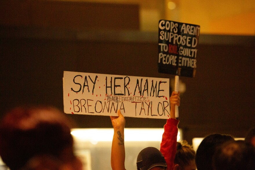 "Photo of protesters holdings signs that read ""Say her name, Breonna Taylor, Black Lives Matter"" and ""Cops aren't supposed to kill guilty people either."""
