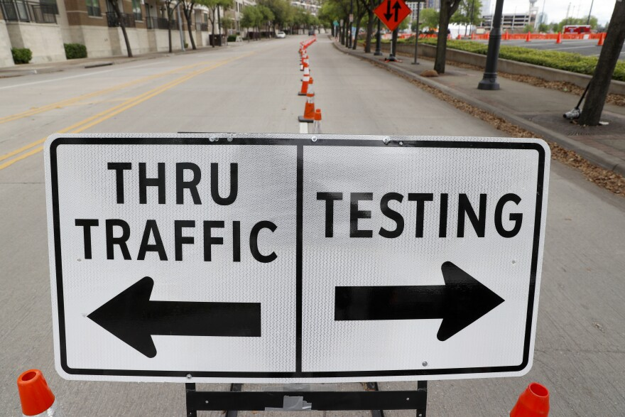 A sign directing drivers is placed near the entrance of a coronavirus test location in Dallas.