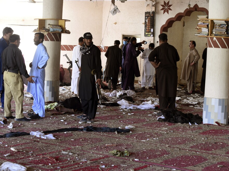 People gather at a mosque following a bomb blast in Kuchlak near Quetta, Pakistan, on Aug. 16. Pakistani police say a powerful bomb went off inside the mosque during Friday prayers. Taliban leader Haibatullah Akhundzada and his relatives frequently attend the mosque. One of his brothers was killed in the blast.