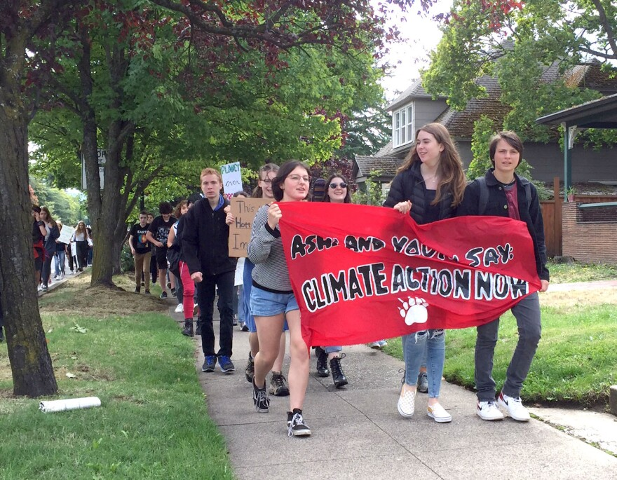 Photo of students with banner on sidewalk.