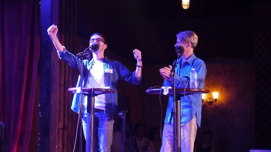 John Cameron Mitchell (right) and contestant Jordan Shavarebi celebrate a victory during their <em>Ask Me Another</em> Challenge.