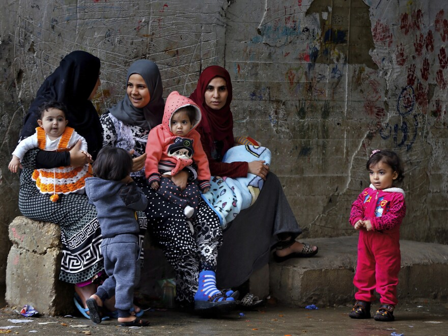 Syrian refugee women hold their children in a refugee compound in the southern port city of Sidon, Lebanon.