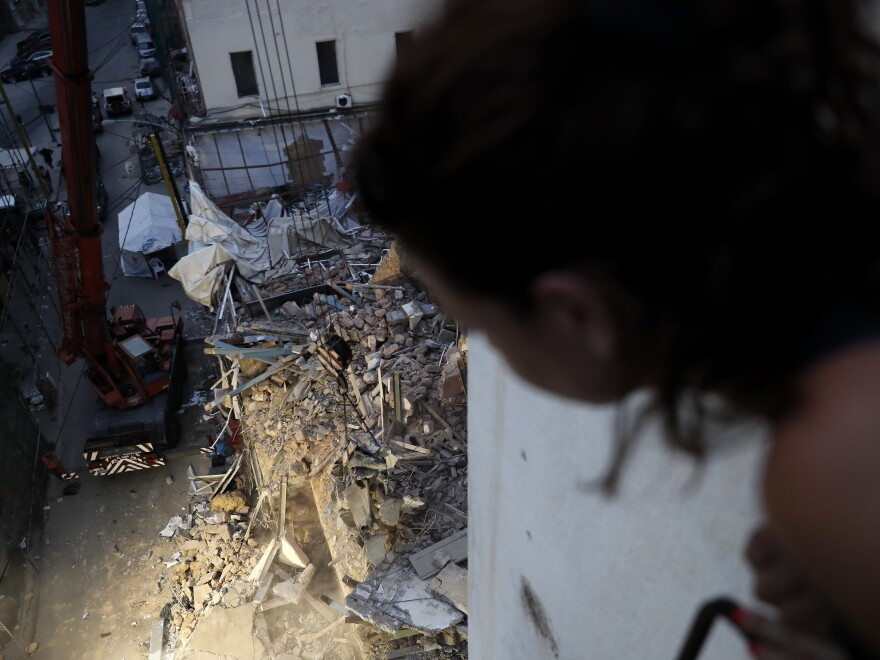 A woman watches from her apartment balcony as a crane removes the rubble of a building after a Chilean rescue team detected signals there may be a survivor at the site in Beirut, Lebanon, on Sept. 4, 2020.