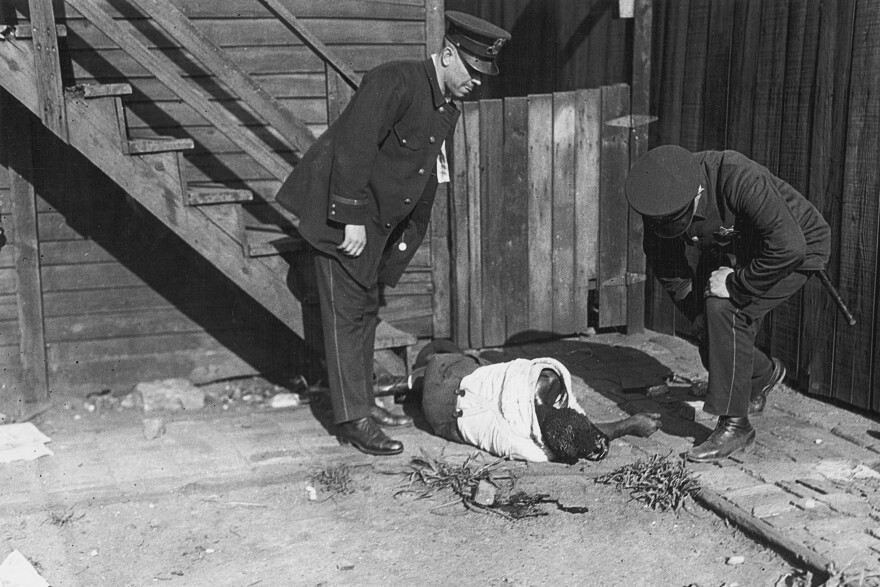 African American victim of race riot stoning lying on ground, with police standing above, Chicago, Illinois, 1919.