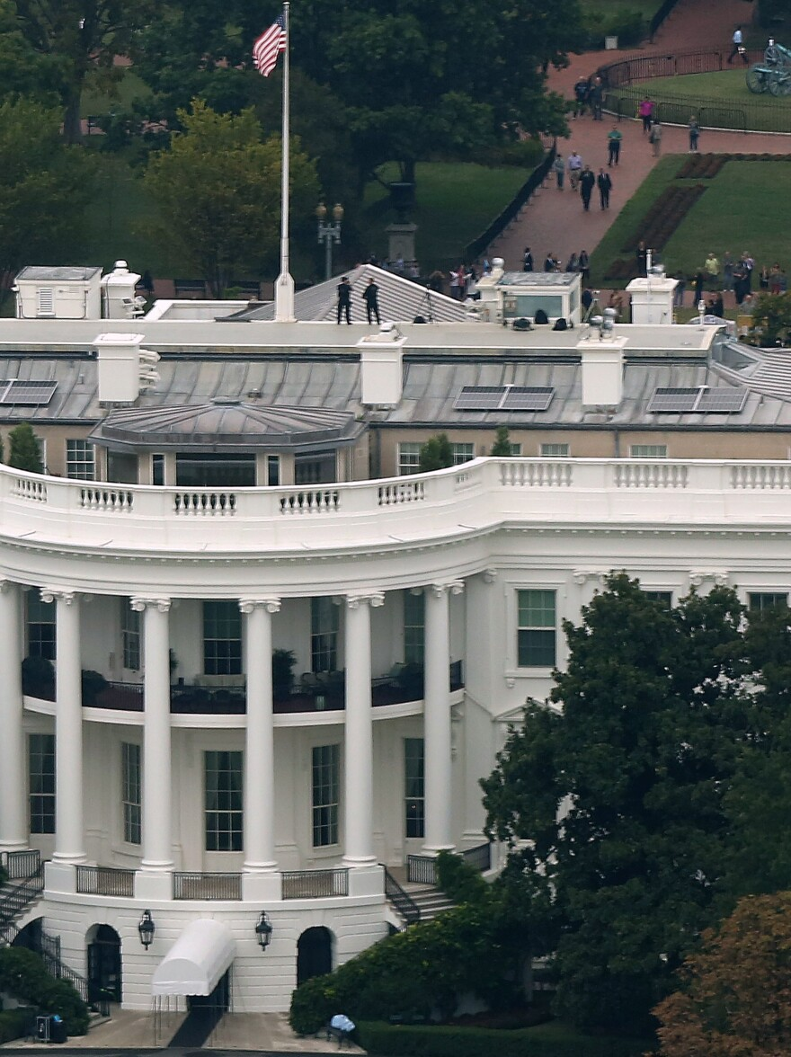 U.S. Secret Service countersniper team members stand on the roof of the White House on Monday.