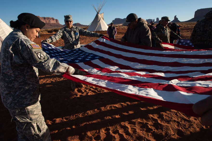 Photo of women and men in military uniform holding open a large american flag, with a tipi in the background.