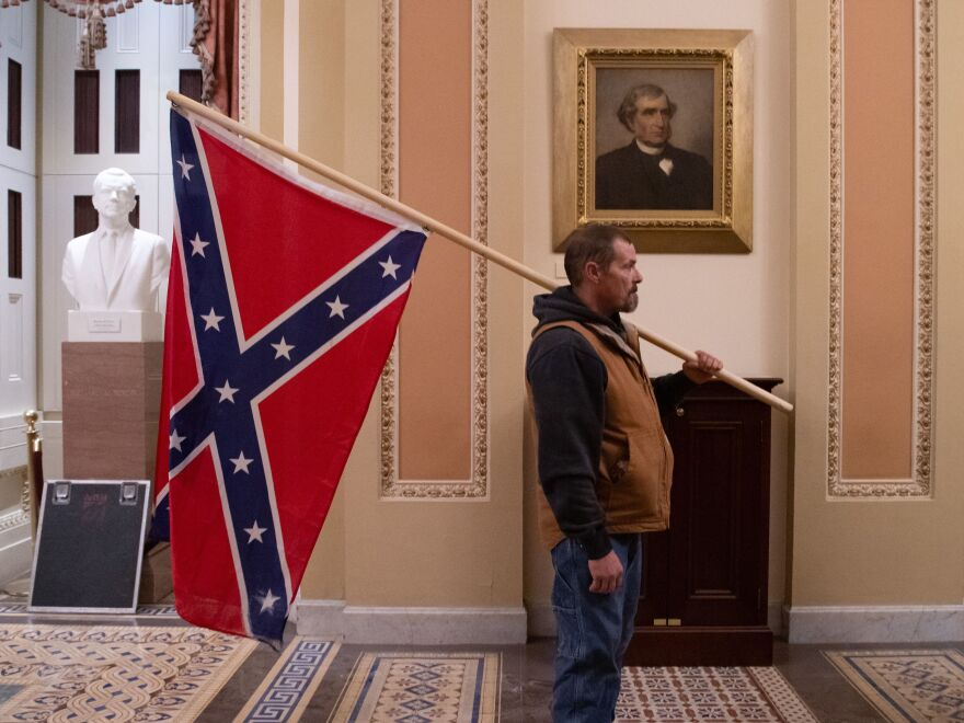 A pro-Trump rioter carries a Confederate flag outside the Senate Chamber during the insurrection at the Capitol on Jan. 6.
