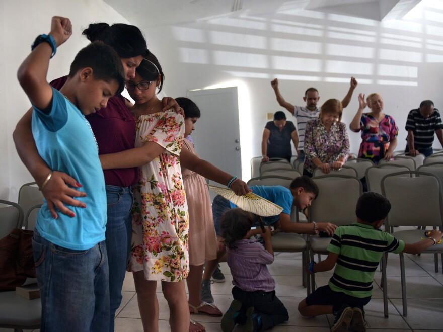 Ada Reyes hugs her children as churchgoers pray.