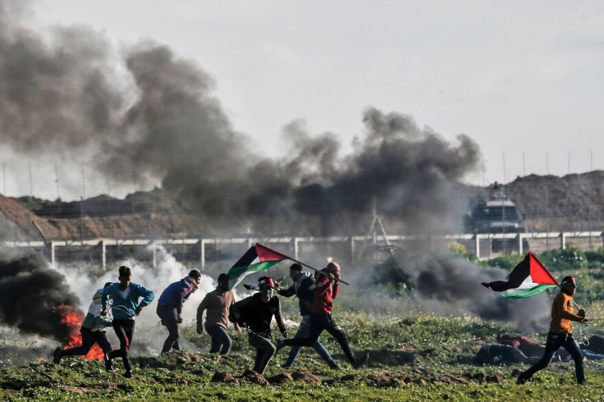 Protesters carry Palistinian flags as they walk past burning tires during a demonstration near the fence along the border with Israel, east of Gaza City, on Feb. 22, 2019.