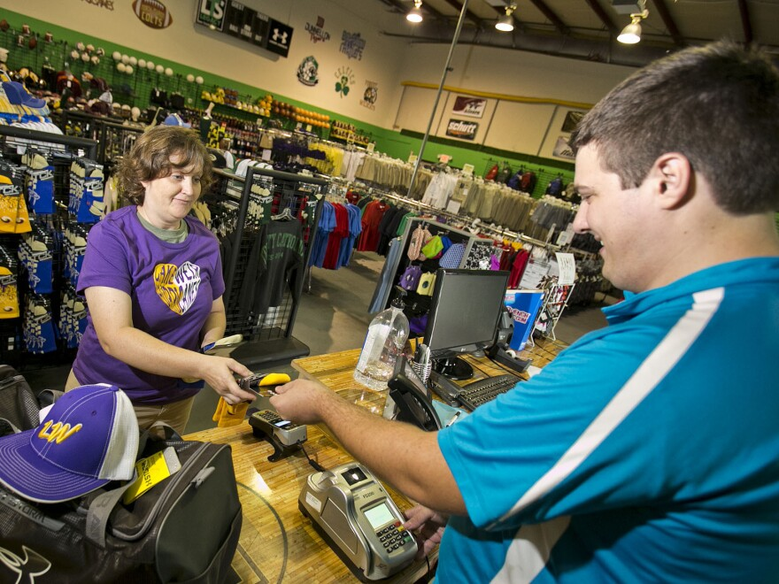 April Thompson makes a purchase at Legacy Team Sales in Ocala, Fla., in September. Economists say October's surprisingly strong job growth will encourage the Federal Reserve to hike interest rates next month. So holiday shoppers may pay more for using credit cards.