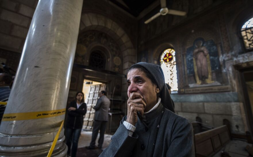 A nun reacts as Egyptian security forces work at the scene of an explosion at the Saint Peter and Saint Paul Coptic Orthodox Church in Cairo Sunday.
