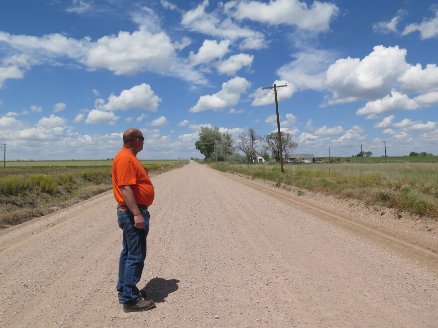 Ault Mayor Butch White stands on a road dividing two farms, one irrigated and one dried up.