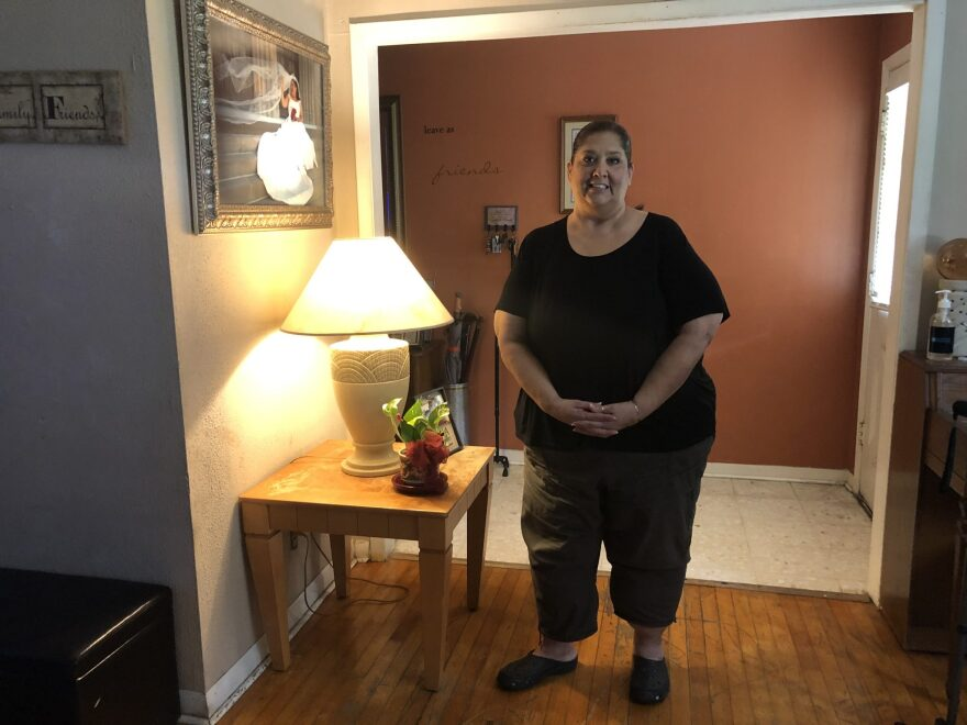 A woman, Veronica Barrientez, stands inside the hallway of her home.