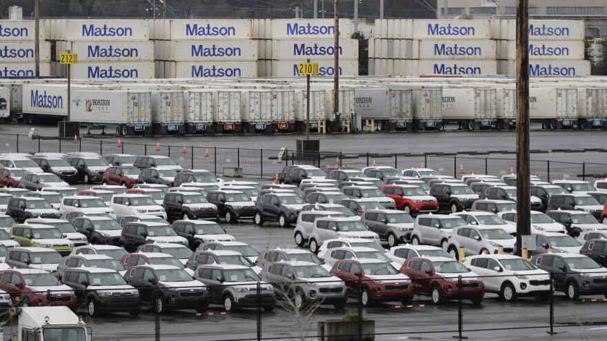 New cars and cargo containers are shown in a staging area, on April 6, 2018, at the Port of Tacoma in Wash. On Wednesday, President Donald Trump ordered the Commerce secretary to look into whether tariffs are needed on vehicles and auto parts imported to the U.S.