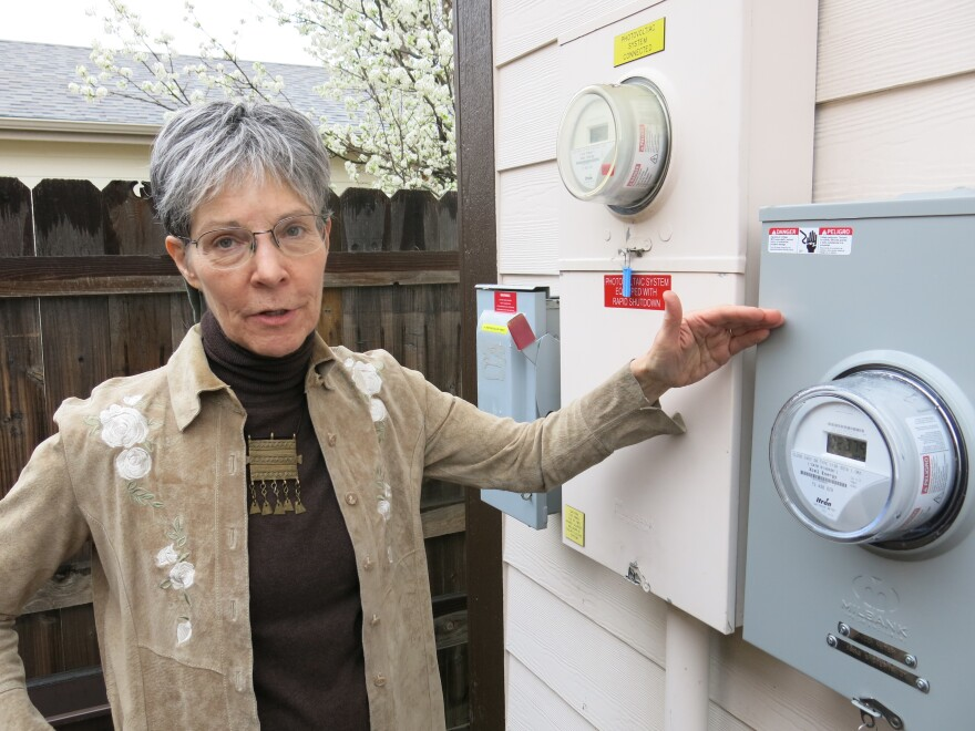 K.K. DuVivier stands by a smart meter that sends electricity back to her utility, Xcel Energy. The Denver home gets credits from Xcel for power that's added back to the grid.