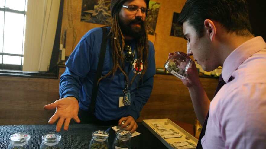 A customer smells a strain of marijuana while being helped by employee Billy Archilla inside the retail marijuana shop at 3D Cannabis Center in Denver.