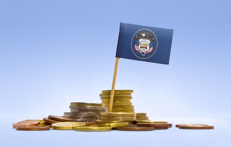 Miniature Utah flag on a toothpick planted in a pile of gold coins.