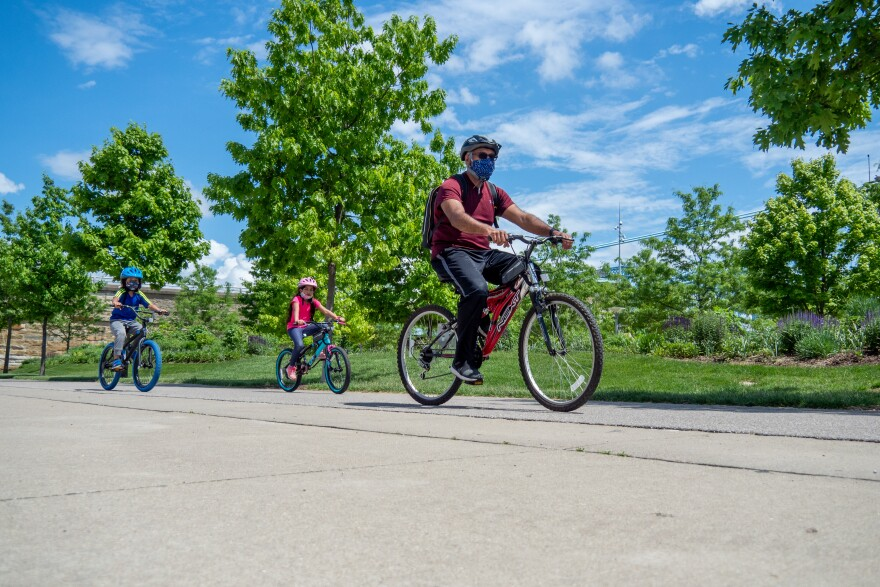 A family wears masks while biking near Smale Park in May. The Cleveland Clinic's Aaron Hamilton says he will wear his mask during outdoor activities where he cannot safely socially distance from other people.