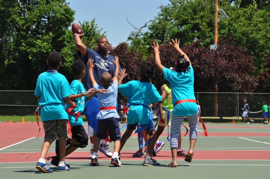 Boys & Girls Club employee Nick Chandler (center) throws a ball to campers at Ferguson Middle School.