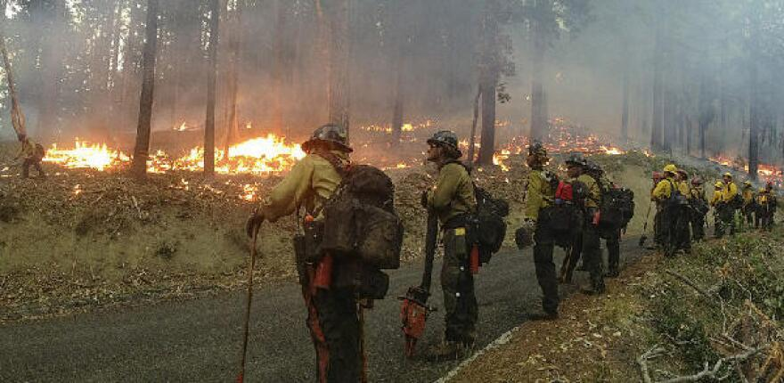 Hot show crew faces a fire along a forest road.