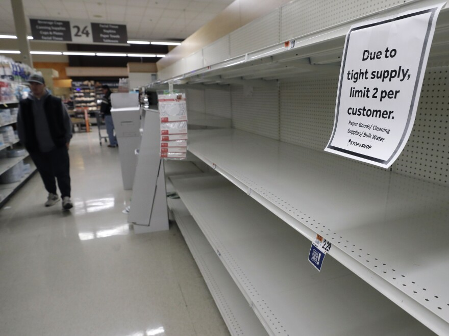 At a grocery store in Quincy, Mass., on March 26, a passerby walks down an aisle with empty shelves where paper towels are normally stocked. Paper towels and toilet paper have sold briskly as people take measures to cope with the coronavirus.