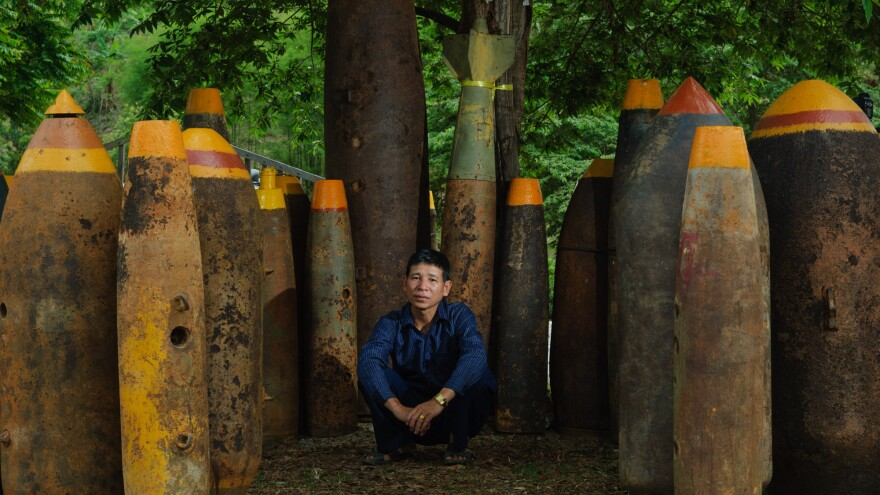 Sang Kham poses amid some of the thousands of bombs he has defused. He's turned the weapons into a shrine to victims of the U.S. bombing campaign.