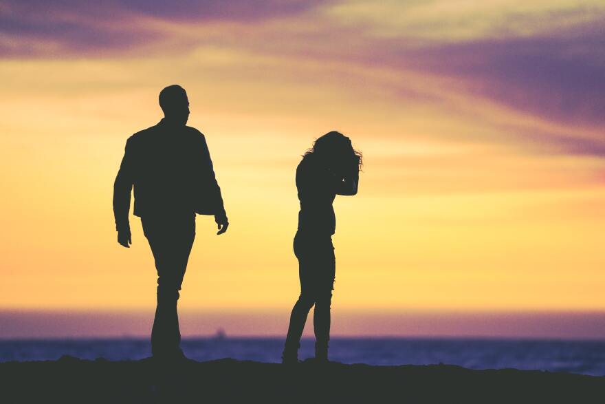 outline of a man and woman in front or orange sky