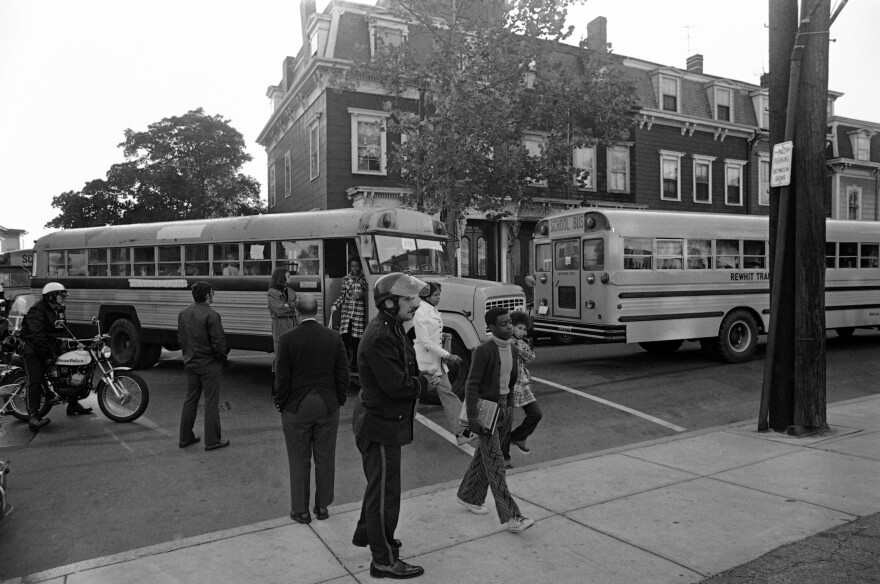 School desegregation continues at South Boston High School, Sept. 24, 1974, with Black students arriving by bus and white students walking from their neighborhood homes.