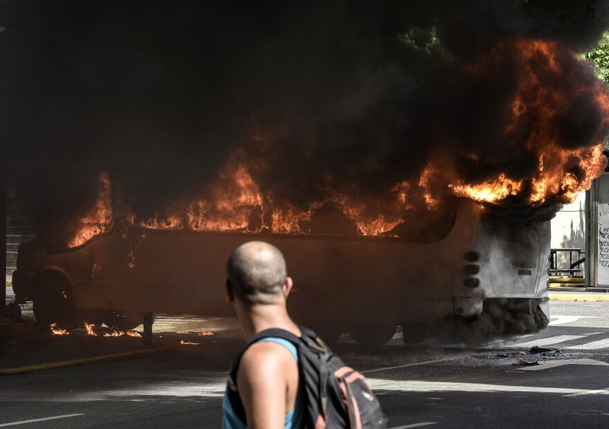 A man stares at a burning bus in Caracas on Saturday. Hundreds of people have been injured in the weeks of near-constant clashes between protesters and police.