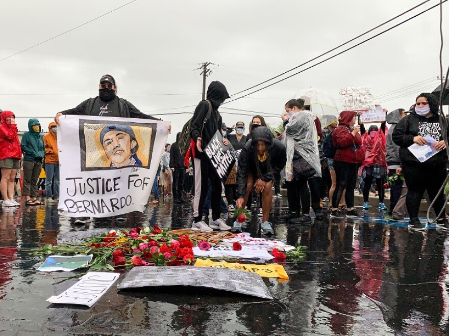 Photo of protesters encircling a pile of discarded roses and signs in a rainy parking lot.