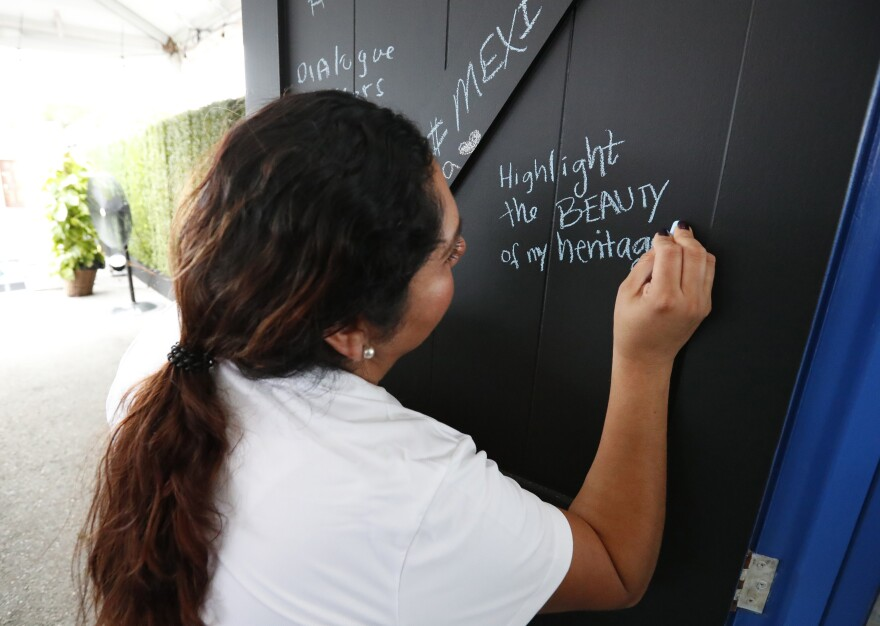 Ivette Diaz writes in chalk on one of the doors from the <em>Common Ground</em> installation. She is with the Libre Institute, one of the groups behind the project, which focuses on discussions around immigration.