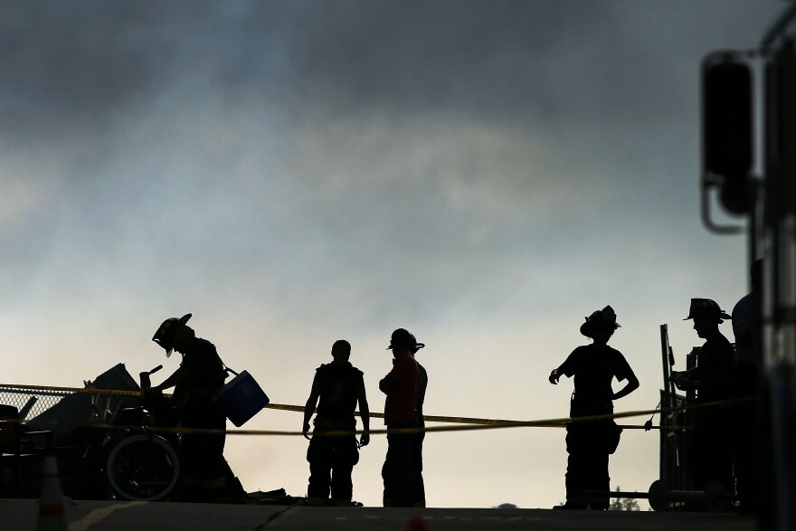 Firefighters stand at the scene of a massive fire that destroyed dozens of businesses along an iconic Jersey shore boardwalk on September 13, 2013 in Seaside Heights, New Jersey.