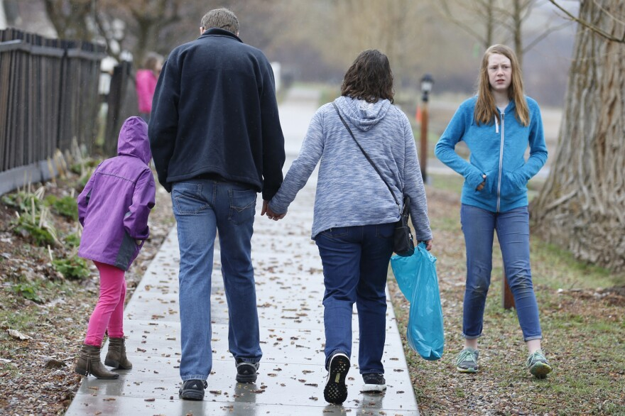 Amy Coulter, center right, and her husband Mark walk together with their children April, 7, left, and Kendra, 12, at the Place Heritage Park in Salt Lake City, April 6, 2018. (Rick Bowmer/AP)