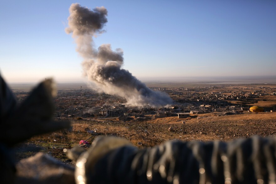 Smoke believed to be from an airstrike billows over the northern Iraqi town of Sinjar on Thursday.