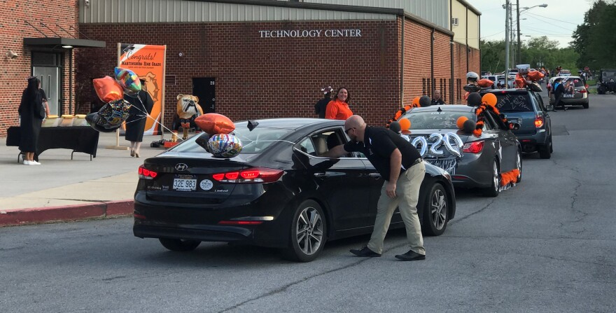 A staff member reaches into a vehicle to deliver a diploma at Martinsburg High School's drive-through graduation on May 26, 2020. The majority of faculty and staff did not wear protective equipment or follow social distancing guidelines to combat the coro